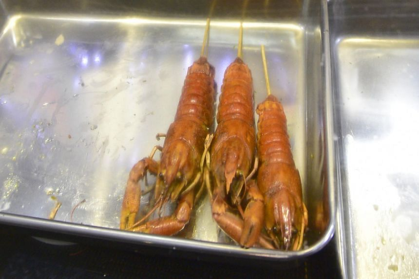 Crawfish sold at a stall at the Geylang Serai bazaar. A woman in China has to consume one kilogram of crawfish each day at her job in Qianjiang.