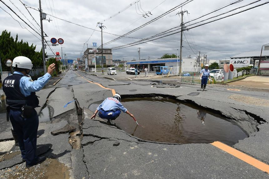 Police checking a collapsed road in Takatsuki following the earthquake yesterday. The epicentre of the temblor was near the residential Takatsuki district, about an hour to the north of Osaka's main tourist area of Dotonbori.