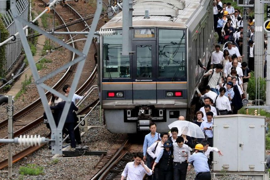 Passengers of a commuter train in Osaka walking on the railway track after service was suspended.