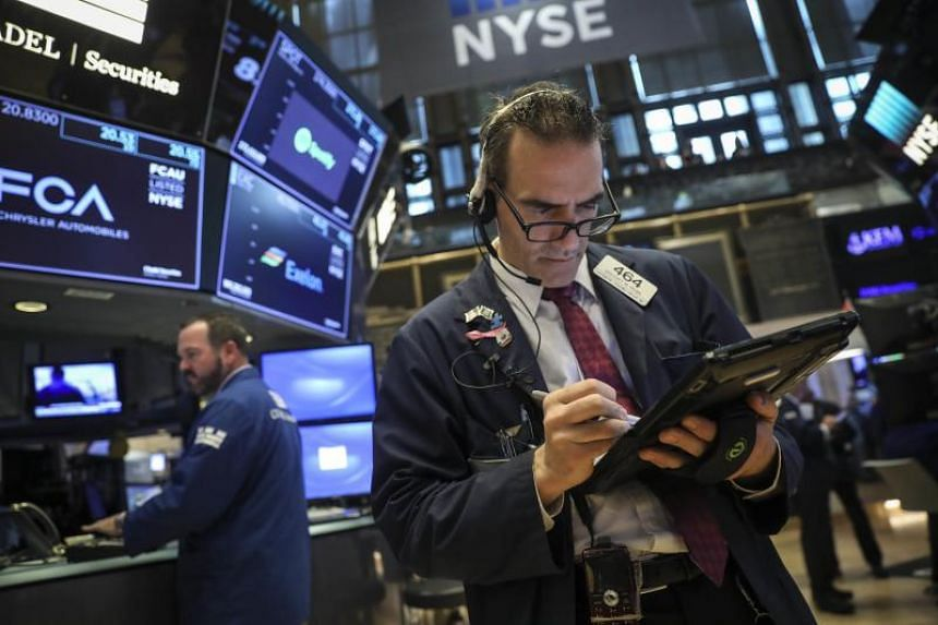 Traders and financial professionals work ahead of the opening bell on the floor of the New York Stock Exchange, on June 19, 2018 in New York City.