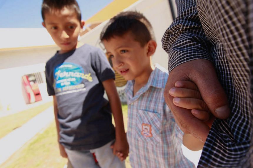 Salvadoran migrant Epigmenio Centeno and his sons, nine-year old Axel Jaret (left) and three-year old Steven Atonay, pose for a photograph outside the shelter House of the Migrant on June 19, 2018.