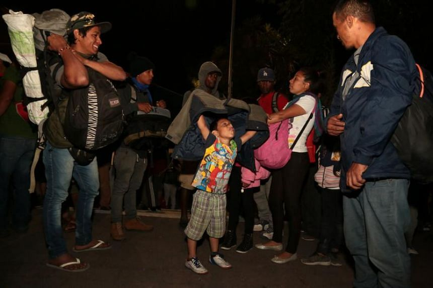 A child gestures next to other Central American migrants taking part in the Migrant Viacrucis caravan towards the United States as they walk towards Nuestra Senora de San Juan de Los Lagos church in Puebla, Puebla state, Mexico, on April 5, 2018.