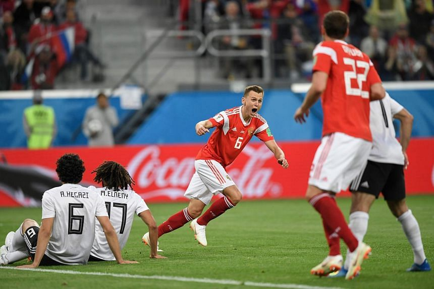 Russia's midfielder Denis Cheryshev (centre) reacts after the team's second goal during the match with Egypt at the Saint Petersburg Stadium, on June 19, 2018.