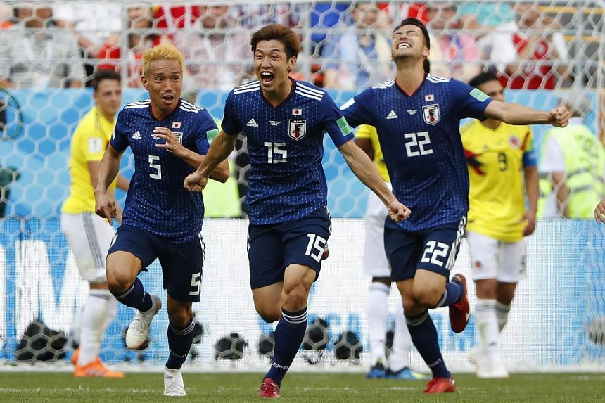 Japan's forward Yuya Osako (centre) celebrates with teammates after scoring a goal during the match with Colombia at the Mordovia Arena in Saransk, on June 19, 2018.