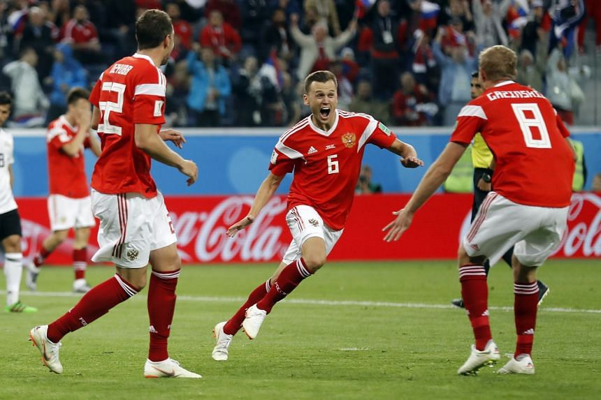 Denis Cheryshev of Russia (centre) celebrates after scoring a goal against Egypt during the World Cup football match in Saint Petersburg, Russia, on June 19, 2018.