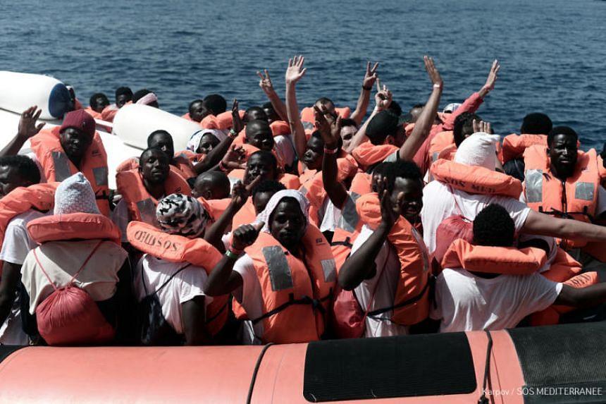 Migrants waving onboard an Italian coastguard ship on June 14, 2018.