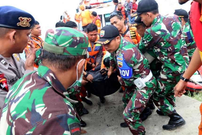Indonesian security forces and rescue workers carry a victim recovered after a ferry sank in Lake Toba, at Tigaras Port in Simalungun, North Sumatra, Indonesia, on June 20, 2018.
