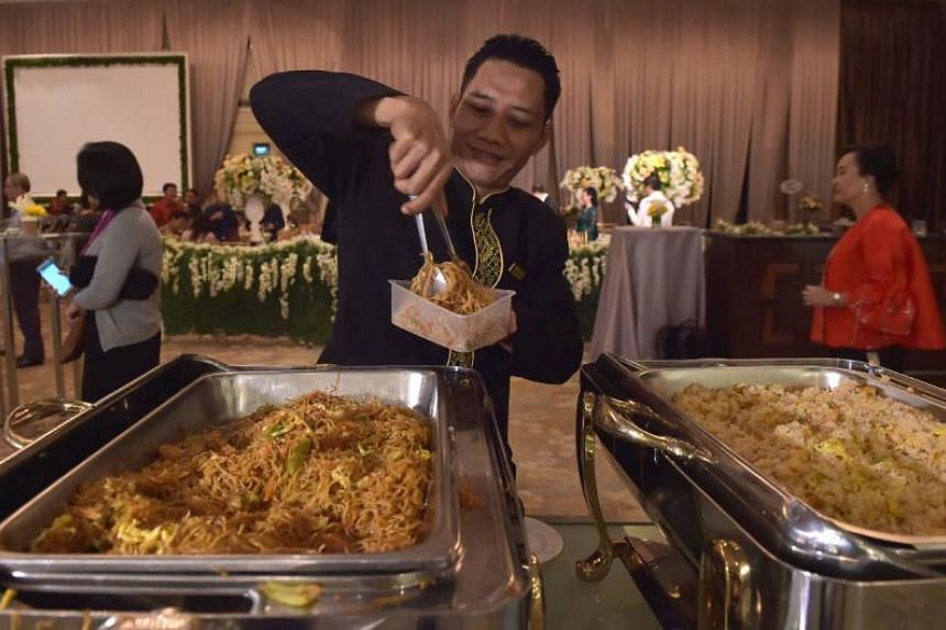 A waiter packing uneaten food for distribution through the programme A Blessing To Share, after a wedding at a hotel in Jakarta.