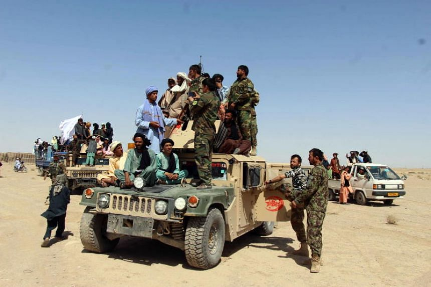 Taleban militants posing with Afghan Army soldiers as they visit the government-controlled areas to greet people as a goodwill gesture amid a three-day ceasefire on the third day of Eid al-Fitr, in Kandahar, Afghanistan, on June 17, 2018.