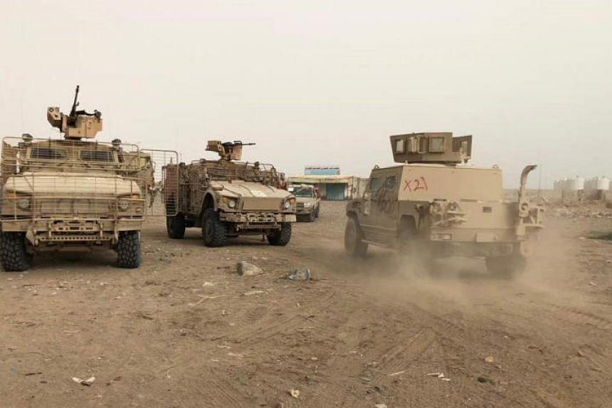 Yemeni pro-government forces backed by the Saudi-led military alliance advance during their fight against Huthi rebels in the area of Hodeida's airport, on June 19, 2018.