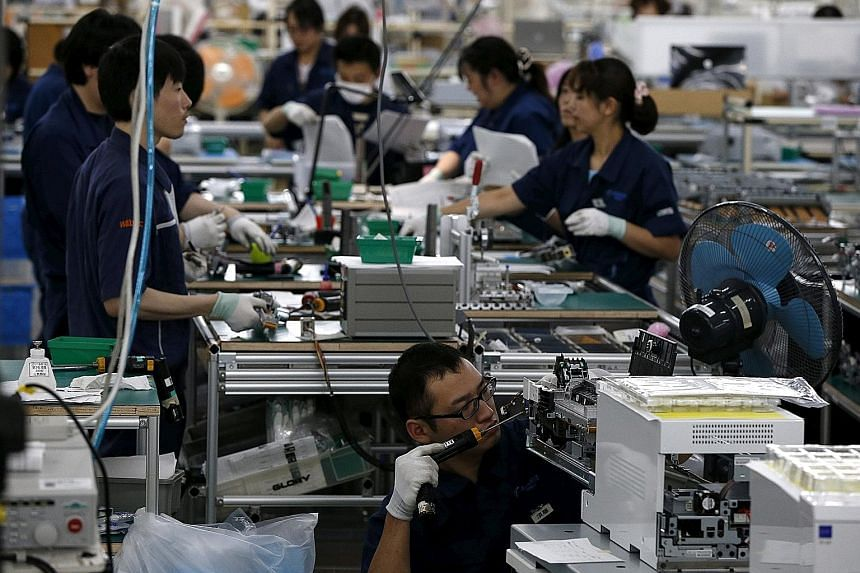 An assembly line at a factory of Glory Limited, a manufacturer of automatic change dispensers, in Kazo, north of Tokyo. Japan manufacturers' confidence is expected to rise over the next three months.