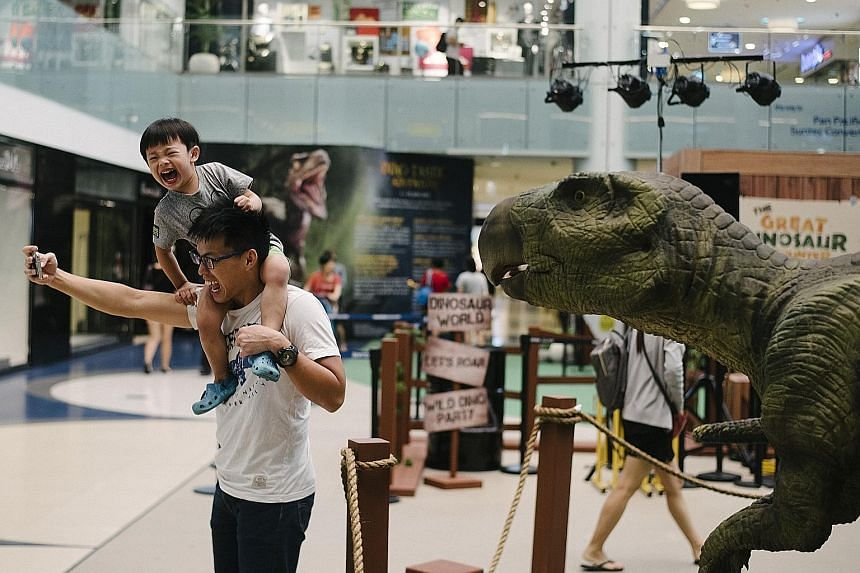 """A father and son posing for a selfie with a dinosaur exhibit, which is part of the Dino-Tastic Adventure event held at the Marina Square atrium. The event showcases animatronic dinosaur exhibits as well as a live show, where families get to """"feed and"""