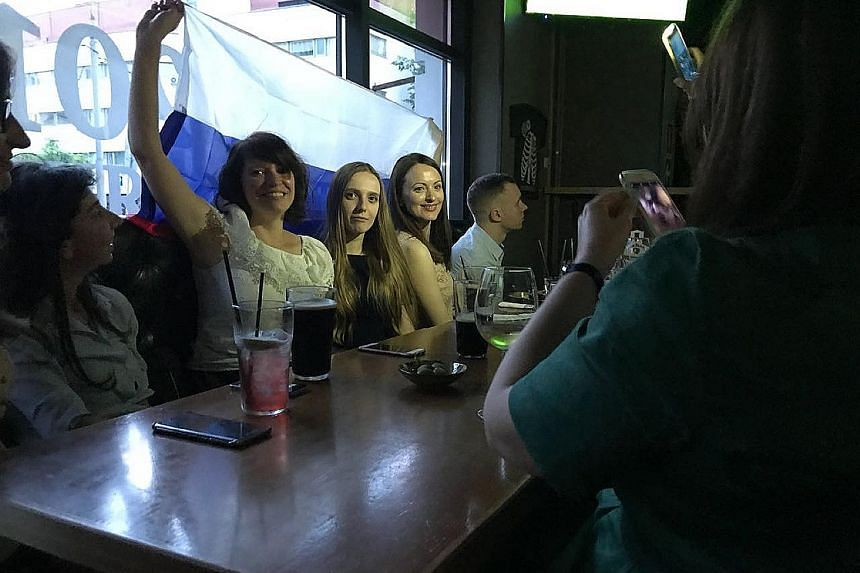 """About 50 fans at the Darlingbar in Moscow watching Russia play Egypt. The locals demonstrate their patriotism by bringing flags, standing to attention during their national anthem and shouting """"Nujen gol!"""" (Russian for: We need a goal.); the celebrat"""