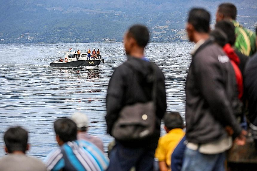 Residents waiting as members of an Indonesian search and rescue team look for victims from the sunken boat in Lake Toba, Sumatra, yesterday. Besides divers and underwater vehicles, about 400 personnel have been deployed to search the huge lake in an