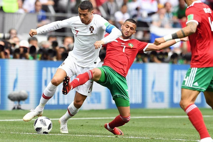 Cristiano Ronaldo of Portugal (left) and Hakim Ziyach of Morocco in action during the FIFA World Cup 2018 group B preliminary round football match between Portugal and Morocco in Moscow, Russia, on June 20, 2018.