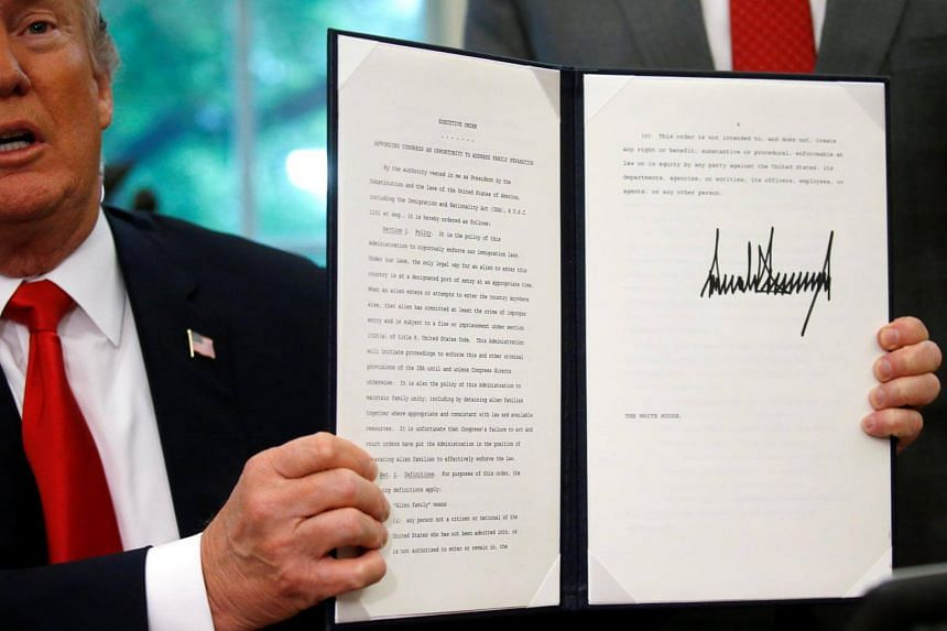 US President Donald Trump displays an executive order on immigration policy after signing it in the Oval Office at the White House in Washington, DC, on June 20, 2018.
