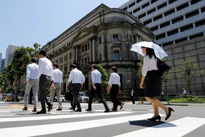 File photo showing people walking past an office building in Tokyo, Japan. A city official reportedly had his pay docked for taking lunch 3 mins early.