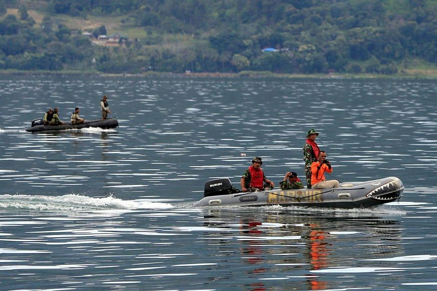 Rescue team members on Lake Toba using rubber boats to find missing passengers from the overloaded Indonesian ferry that sank. Official estimates list 193 people to be currently missing.