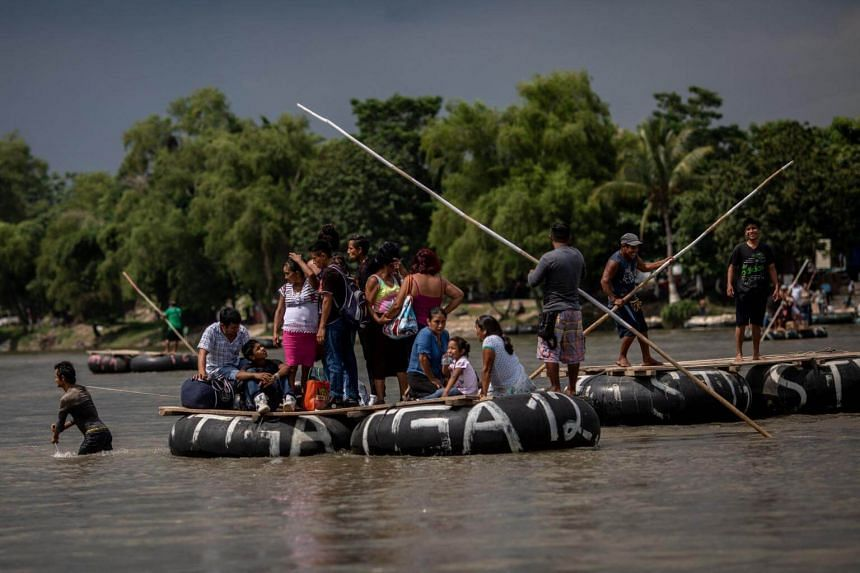 Migrants using handmade rafts crossing the river that separates Guatemala from Mexico on June 19, 2018.