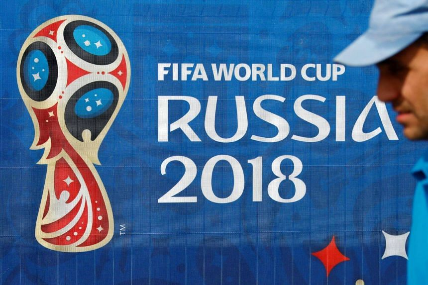 A man is seen next to the FIFA World Cup logo at the Saint Petersburg Stadium, on June 11, 2018.