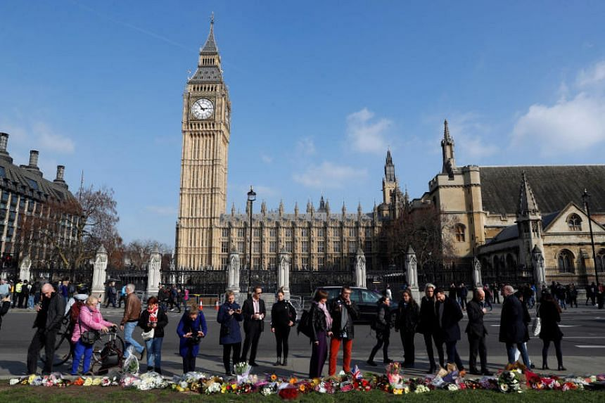 People look at tributes left in Parliament Square following a recent attack in Westminster, London, Britain, on March 24, 2017.