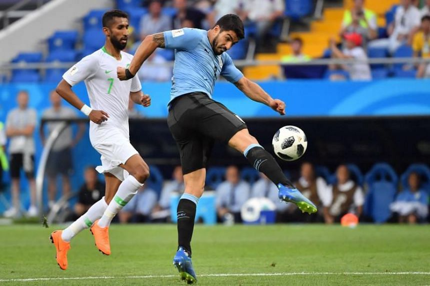Uruguay's forward Luis Suarez (right) shoots beside Saudi Arabia's midfielder Salman Al-Faraj during the Russia 2018 World Cup Group A football match between Uruguay and Saudi Arabia at the Rostov Arena in Rostov-On-Don on June 20, 2018.