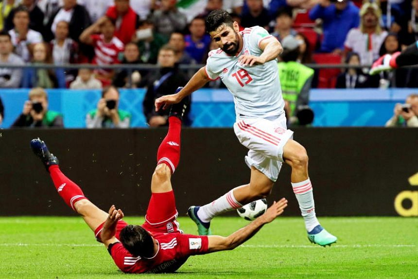 Morteza Pouraliganji (left) of Iran in action against Diego Costa of Spain during the Fifa World Cup 2018 group B preliminary round soccer match between Iran and Spain in Kazan, Russia, on June 20, 2018.