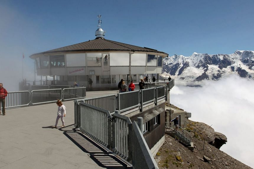Tourists are seen in front of the world's first revolving restaurant, known as Piz Gloria from the 1969 James Bond movie On Her Majesty's Secret Service, which was filmed there, on the peak of the Schilthorn mountain at the Bernese Oberland, Switzerl