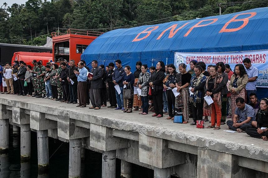 Family members of missing passengers attending a prayer session yesterday, after a ferry sank in Lake Toba in Sumatra on Monday.