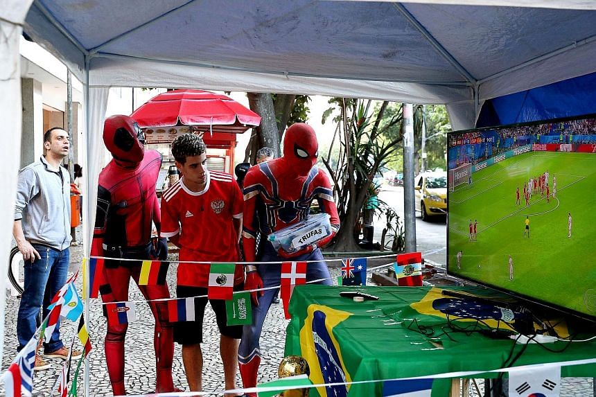 """SAY WHAT? """"Maybe we do not have Iniesta or Ronaldo, but we do have a Big HEART for a Bigger DREAM!"""" An Iranian fan getting his message across during his team's 1-0 defeat by Spain. SWEET TWEET Mohamed Salah gets mummified by Uruguay's Diego Godin and"""
