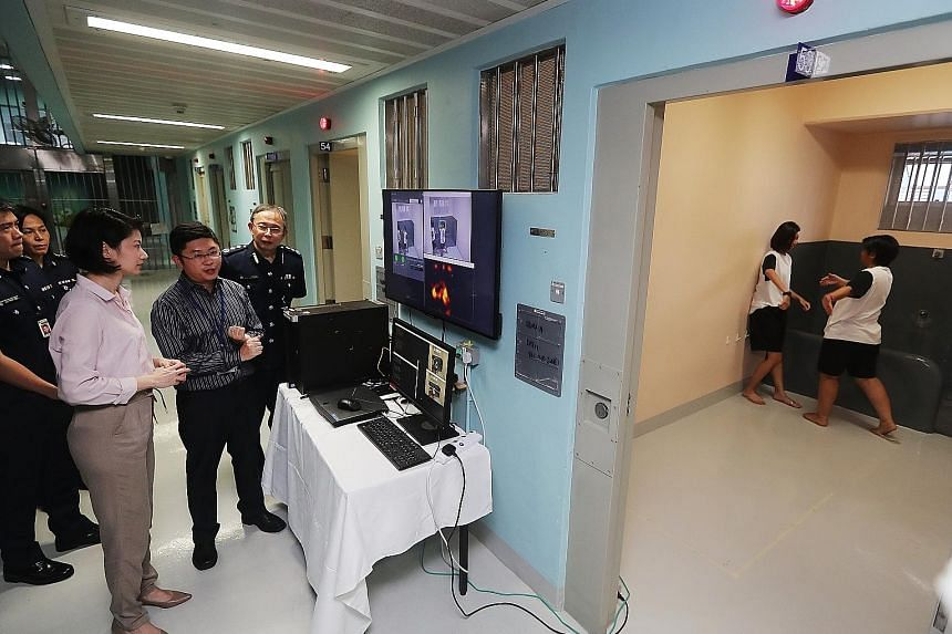 Senior Parliamentary Secretary for Home Affairs and for National Development Sun Xueling watching a demonstration of the prototype video analytics system yesterday, as prison officers simulated a fight between inmates in a cell. The analytics system
