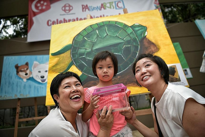 Sophie Wong with her mother, Madam Elizabeth Lim (right), and her grandmother, Madam Wong Moi Yong, 58. Behind them is their terrapin painting. Housewife Norine Nazura Johari and her four children (from left) - Danish, five; Alya, seven; Rayyan, nine