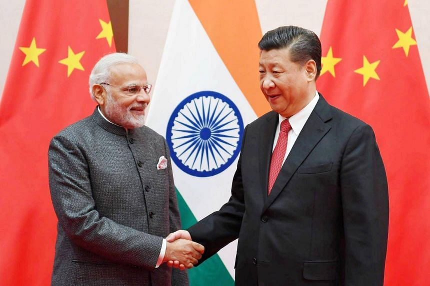 Indian Prime Minister Narendra Modi (left) shakes hands with Chinese President Xi Jinping during the 18th Shanghai Cooperation Organisation Summit in Qingdao, China, on June 9, 2018.
