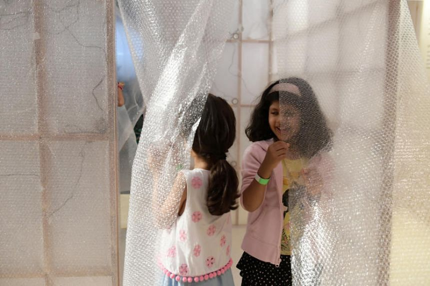 Children at a bubble-wrapped sound booth with experimental sound recordings based on an audio book.