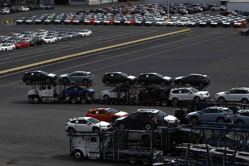 Brand new cars sit on a truck that is leaving a lot at the Auto Warehousing Company near the Port of Richmond on May 24, 2018.