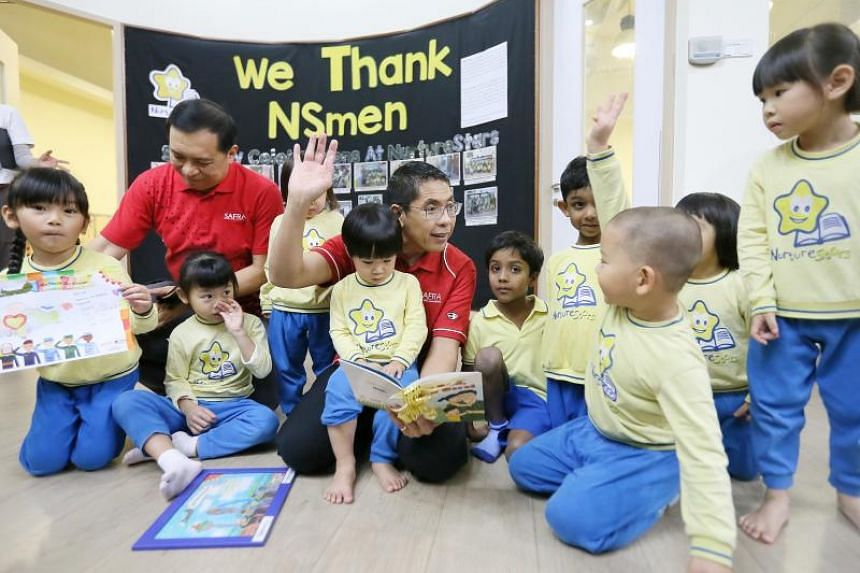 Senior Minister of State for Defence and Foreign Affairs Maliki Osman, who is president of Safra, reading a book to NurtureStars Preschool children at the school's Safra Jurong centre on June 22, 2018.