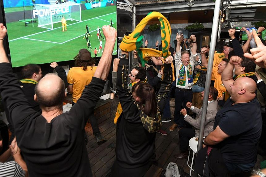Australian fans react in a Melbourne pub, as they watch on giant screens Australia play Denmark in their Russia 2018 World Cup Group C football match on June 21, 2018.