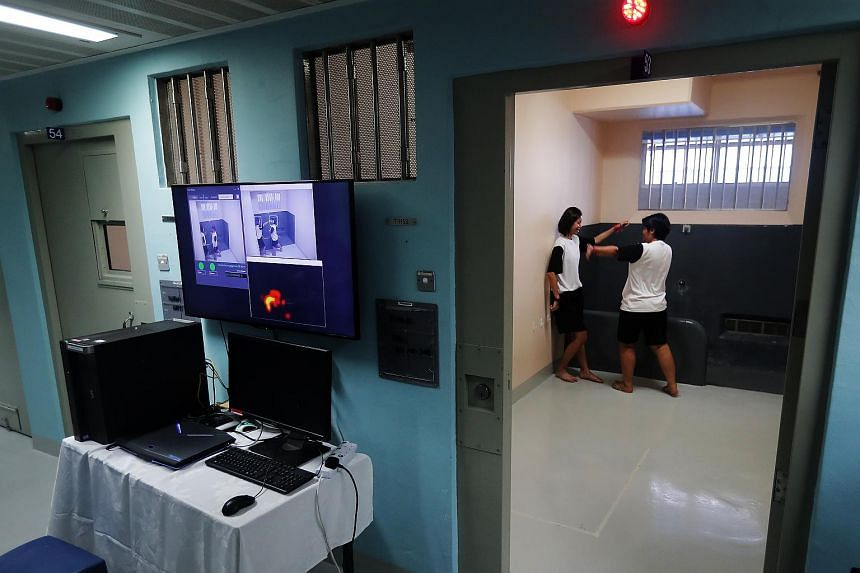 Prisons officers demonstrating how the new prototype video analytics called Avatar, also known as the Human Behaviour Detection System, will work. It is currently on trial at the Changi Prison Complex.