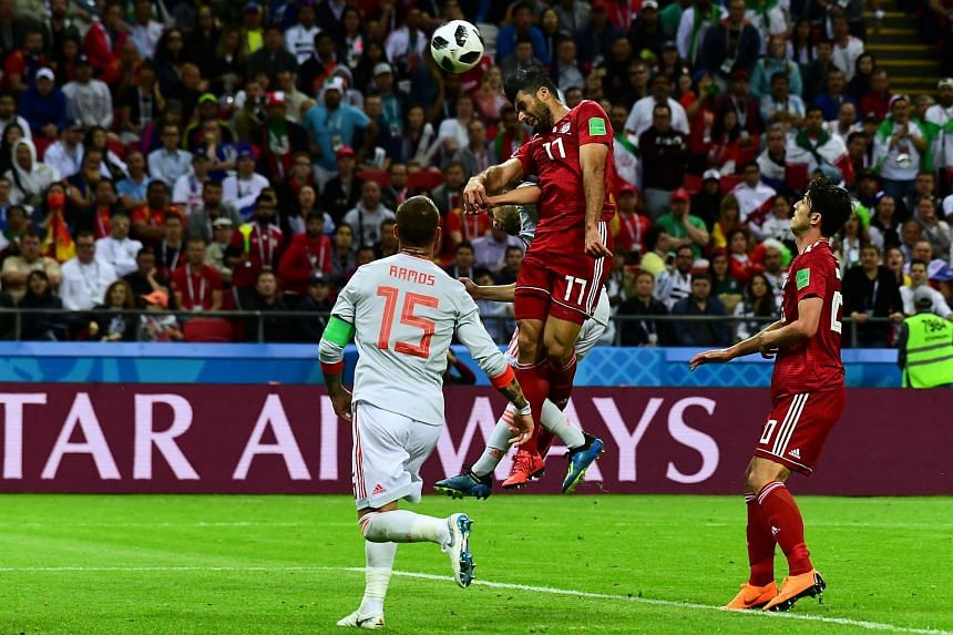 Iran's forward Mehdi Taremi (centre) heads the ball during the Russia 2018 World Cup Group B football match between Iran and Spain at the Kazan Arena in Kazan, on June 20, 2018.