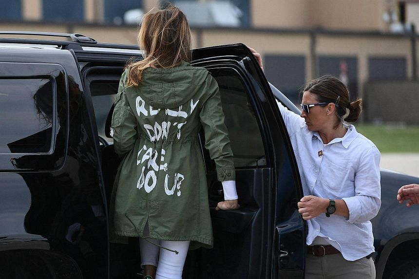 """US First Lady Melania Trump arrives back in Washington from Texas wearing a rain jacket sporting the phrase """"I Really Don't Care. Do U?"""" on the back."""
