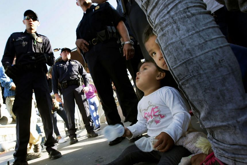 Migrant families from Mexico hoping to seek asylum speaking to US Customs and Border Protection officers at the Paso del Norte international border crossing bridge in Ciudad Juarez, Mexico, on Wednesday. Republican and Democratic senators are divided