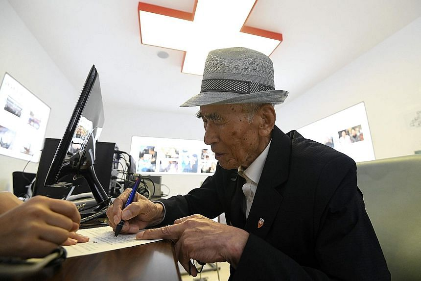 A South Korean filling in an application for the inter-Korean family reunion scheme at the Red Cross office in Seoul yesterday.