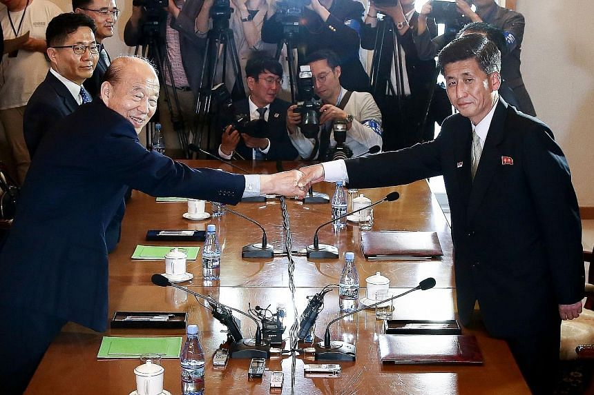 South Korea's chief delegate Park Kyung-seo (far left) shaking hands with his North Korean counterpart Pak Yong Il during talks at North Korea's Mount Kumgang resort yesterday, in a photo released by the South's Unification Ministry.