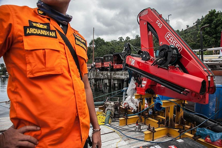 Members of the search-and-rescue team preparing to deploy sonar equipment at the Lake Toba ferry port. A total of 193 people are listed as missing, their bodies believed to be trapped inside the sunken ferry at the bottom of the lake.