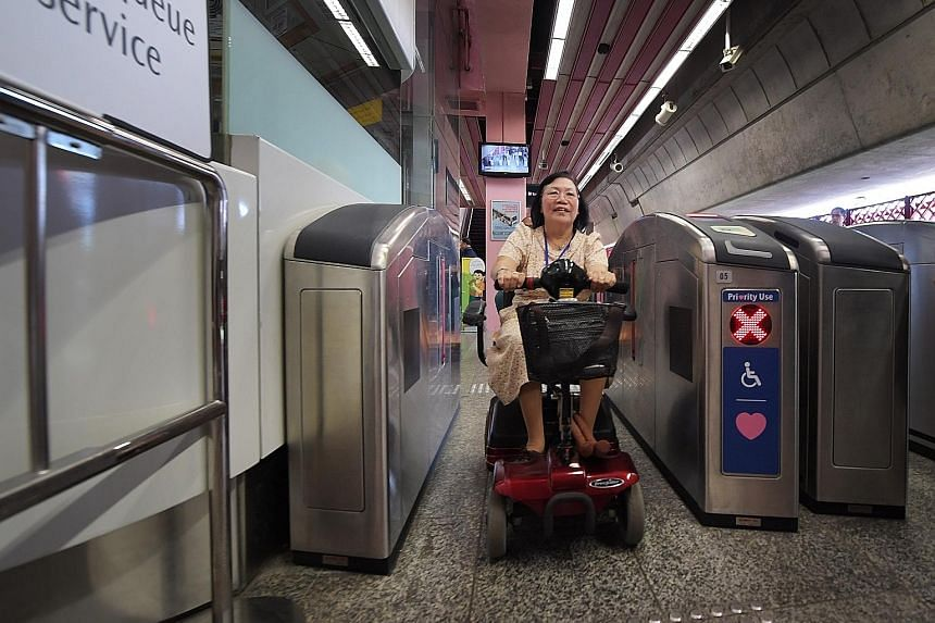 Madam Chew Bee Que, 67, trying out the hands-free fare gate at Redhill MRT station yesterday. Selected commuters can use a radio-frequency ID card or a Bluetooth-enabled mobile device with a specific application to pay.