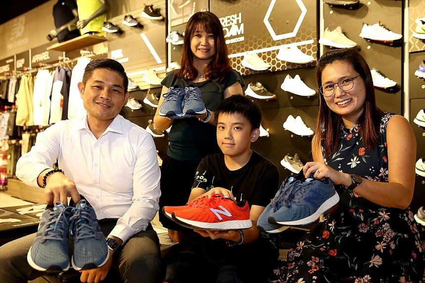 From left: ST Run participants Jason Oh, 45; Lina Lim, 51; Tan Kai Rui, 11; and Loh Chen Lin, 41, receiving their New Balance shoes as part of an incentive to get runners to sign up early. The event's sixth edition will take place on Sept 23, startin