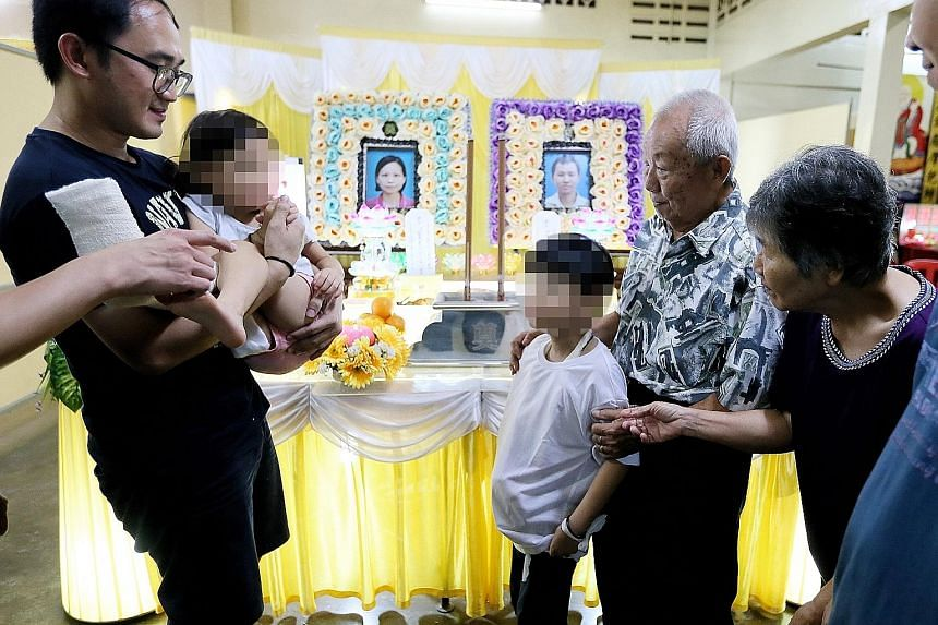 Chua Jun Xian, eight, and sister Xin Rou, five, the children of the couple who died in the crash, with their grandparents, Mr Chua Huat Chuan, 78, and Madam Sii Bee Tee, 69, and another relative at the wake in Seremban.