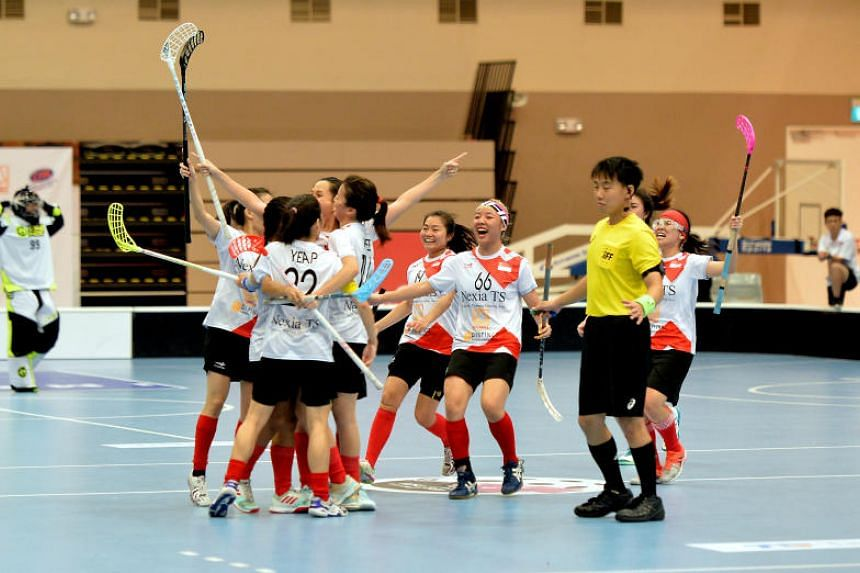 The Singapore women's floorball team celebrate after the final whistle, on June 23, 2018. They defeated Thailand 4-1.