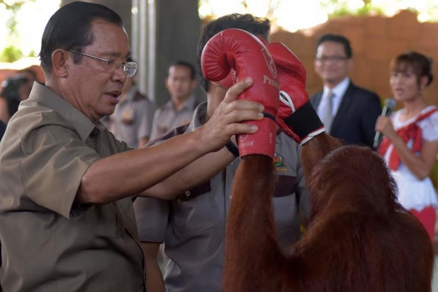 Cambodian Prime Minister Hun Sen holds an orangutan after a kickboxing performance during the inauguration of Phnom Penh Safari on June 23, 2018.