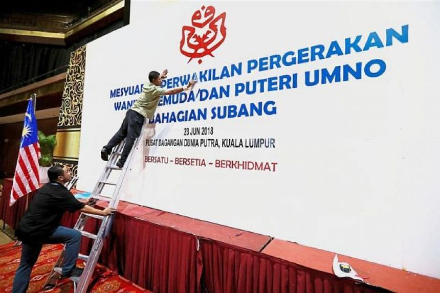 Workers preparing the stage for the Subang Umno division meeting at PWTC, on June 23, 2018.